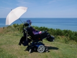 Woman in wheelchair, seen from behind, sat at the edge of a cliff looking out to sea. A parasol shades her from the sun
