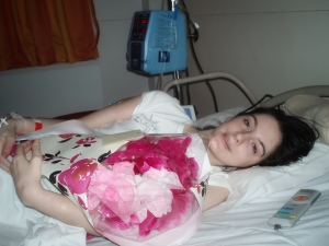 Emily Collingridge lying in a hospital bed, holding a bunch of flowers