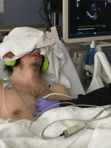 A young man having an echocardiogram. His eyes are covered by a blanket and he wears ear defenders.