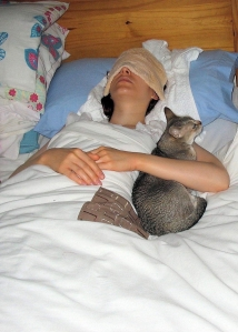A young woman lies ill in bed with a flannel over her eyes.