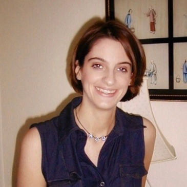 A young woman smiles brightly at the camera. She has short, dark hair and wears a blue top.