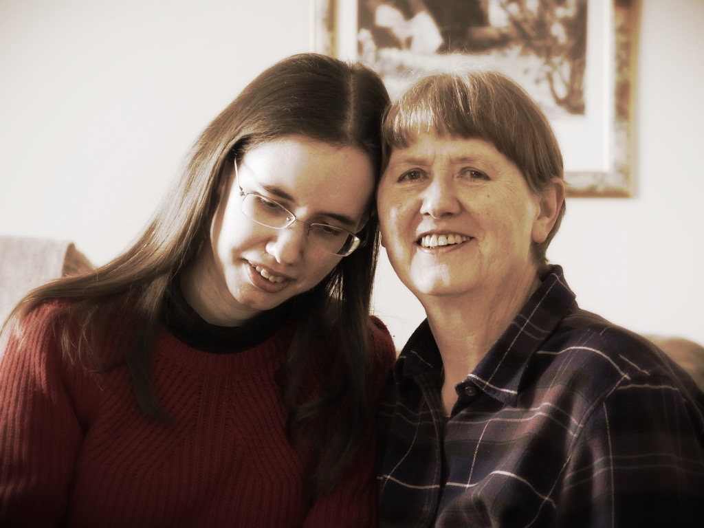 Two women sit with their heads resting supportively together. One looks slightly downwards. The other smiles at the camera.