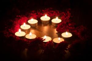 Small candles arranged in a circle on a table, with red flowers in shadow around the edge