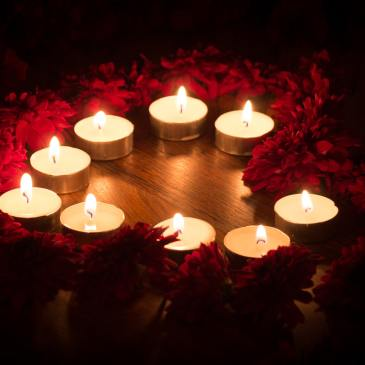 Small candles are arranged on a table in a shape that loosely resembles a heart. Red flowers are in shadow around the edge.