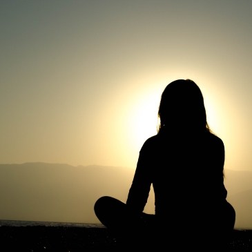 A silhouetted woman is sat on the ground. She is looking across a valley at the sun
