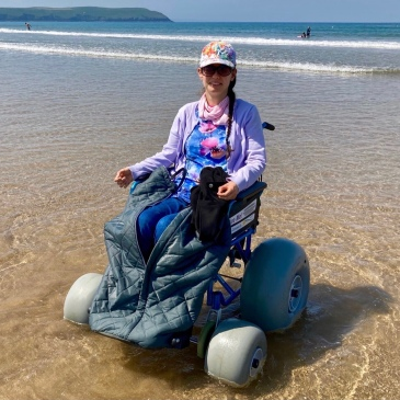Naomi sits at the edge of the sea in a beach wheelchair (which has special large wheels for the sand). She wears sunglasses and a multi-coloured cap, and is smiling at the camera. She is wearing a blue and pink top with a flower pattern, and a pale purple cardigan. Her jeans are partially covered by a wheelchair leg cover. It is a bright, sunny day.