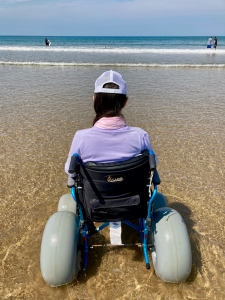 Naomi sits in a wheelchair at the edge of the sea. The camera is behind her. The sea and sky are blue.