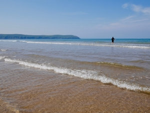 The sea as seen from the shore, looking out towards the horizon and headland. The sea is clear and sparkling in the foreground, and blue further out. A surfer stands in the waves.