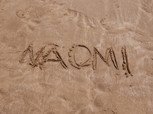 A close-up shot of 'Naomi' written in the sand
